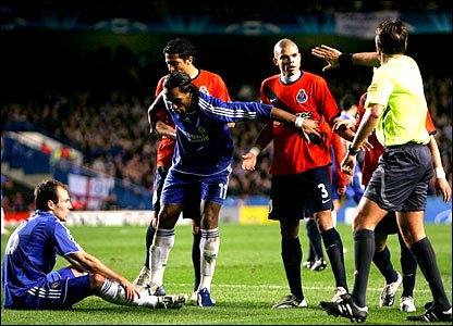 Arjen Robben, of Chelsea, sits on the floor, pouting. Didier Drogba ostentatiously holds back two Porto players, while the referee approaches.
