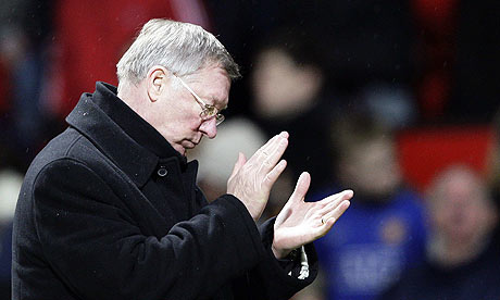 Alex Ferguson, wearing a coat, about to clap