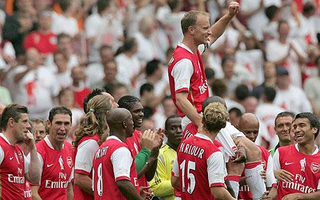 Dennis Bergkamp is raised on the shoulders of his Arsenal teammates. Martin Keown looks funny in the background.