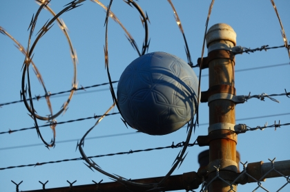 A football suspended in barbed wire